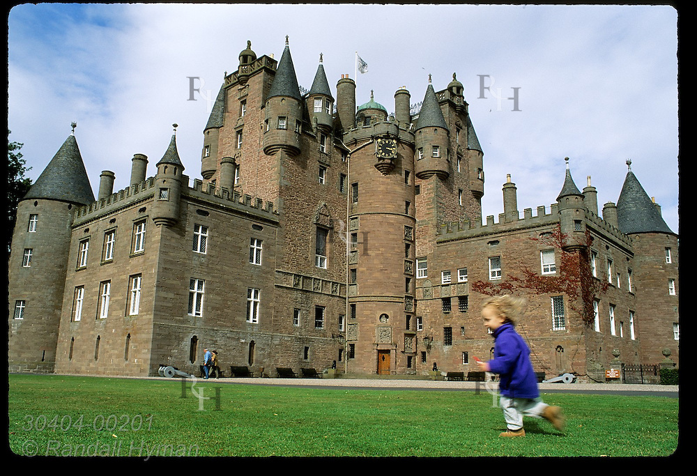 Child runs across lawn in front of Glamis Castle, childhood home of Queen Mother and setting for Macbeth; Glamis, Angus, Scotland.