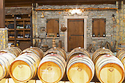 Oak barrels and bottles in the winery. A mock up of a traditional village house. Hercegovina Produkt winery, Citluk, near Mostar. Federation Bosne i Hercegovine. Bosnia Herzegovina, Europe.