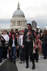© licensed to London News Pictures. London, UK 13/10/2012. People with zombie costumes and make-ups walking on Millennium Bridge as more than 2,000 'zombies' celebrating World Zombie Day on 13/10/12 in London. Photo credit: Tolga Akmen/LNP