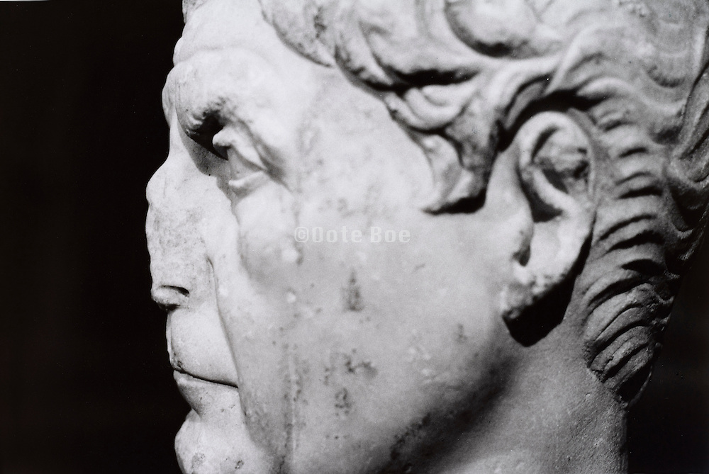 Carved sculpture of a man with nose missing