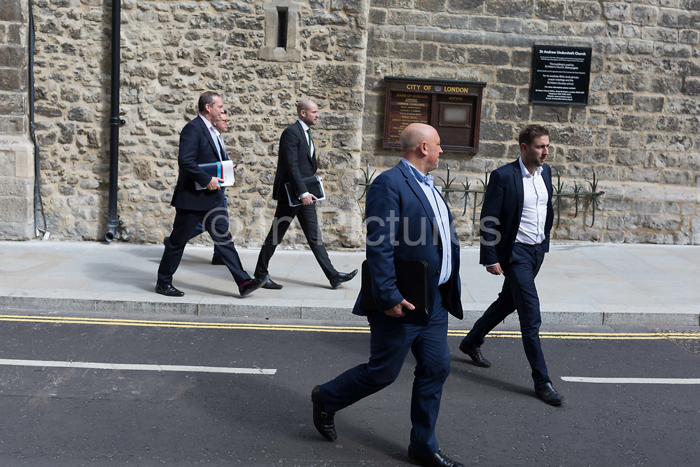 Businessmen walk along St. Mary Axe street in the City of London, the capitals financial district, on 10th May 2019, in London, England.