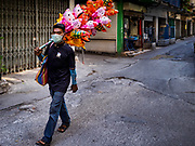 17 DECEMBER 2018 - BANGKOK, THAILAND: An inflatable toy seller walks through a working class neighborhood behind Siam Paragon, an exclusive mall in central Bangkok. According to Credit Suisse Global Wealth Databook 2018, which surveyed 40 countries, Thailand has the highest rate of income inequality in the world. In 2016, Thailand was third, behind Russia and India. In 2016, the 1% richest Thais (about 500,000 people) owned 58.0% of the Thailand's wealth. In 2018, they controlled 66.9%. In Russia, those numbers went from 78% in 2016, down to 57.1% in 2018. The Thai government disagreed with the report and said the report didn't take government anti-poverty programs into account and that Thailand was held to an unfair standard because most of the other countries in the report are developed countries in the Organisation for Economic Co-operation and Development.    PHOTO BY JACK KURTZ