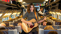 © Licensed to London News Pictures. 08/04/2015. St Pancras International Station, London, UK.  Natalie Shay, a 16 year old musician from Enfield, North London, and a current student at the BRIT School for performing arts on board the Eurostar train to perform in Paris.  Her trip comes as a result of being awarded the Eurostar prize as well the Youth Category in last year's Gigs busking competition, organised by City Hall.  The talented singer-songwriter has already picked up several music awards, in addition to her Gigs accolades, including the Undiscovered Talent category at the 2014 London Music Awards, as well as playing at major venues around London, including the Roundhouse and the 100 Club. Photo credit : Stephen Chung/LNP