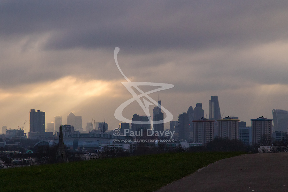 Primrose Hill, London, February 15th 2015. A shaft of sunlight illuminates Docklands on a chilly early morning on Primrose Hill, overlooking London's skyline.<br /> ///FOR LICENCING CONTACT: paul@pauldaveycreative.co.uk TEL:+44 (0) 7966 016 296 or +44 (0) 20 8969 6875. ©2015 Paul R Davey. All rights reserved.