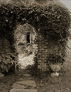 Manhasset, New York, U.S., September 16, 2018.  Sunlit yard is seen through ivy covered archway in brick wall of Elderfields Preserve, during Reception for The Art Guild exhibition in late summer.