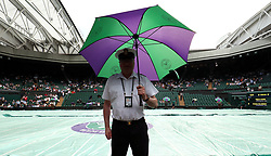 A member of the armed forces shelters from the rain on centre court on day three of the Wimbledon Championships at the All England Lawn Tennis and Croquet Club, Wimbledon.