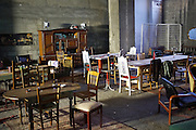 """The Freegan Pony restaurant in the early morning, with no electricity. The furniture is donated by Emmaus.<br /><br />The Freegan Pony is an alternative restaurant housed in a squat. It was founded in 2015 by Aladdin Charni with three other collaborators. The restaurant specialises in cheap vegetarian cuisine, serving meals which guests reserve a place through a Facebook group, paying €2 a meal. The restaurant meals contain unsold and donated food, collected from wholesellers at the Paris Rungis vegetable market. The Freegan Pony is located at the Porte de la Vilette on the outskirts of Paris, at the entrance to the peripherique outer circle motorway.<br /><br />Freegans are people who employ alternative strategies for living based on limited participation in the conventional economy and minimal consumption of resources. Freeganism is the practice of reclaiming and eating food that has been discarded. People who attempt to live an ethical lifestyle by reusing trash and rubbish thrown away by others.<br /><br />Freeganism is an ill-defined activity and is a subset of the larger anti-capitalist and environmental protest movements. It embraces alternative, anti-consumerist lifestyles. Freegan practices also include co-operative living, squatting and """"freecyling"""", or matching things that people want to get rid of with things other people need"""