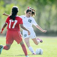 Grants Pirate Marissa Trujillo (16) likes up a kick ahead of  Valencia Jaguar Vanessa Viezca (17) at Grants High School Thursday.