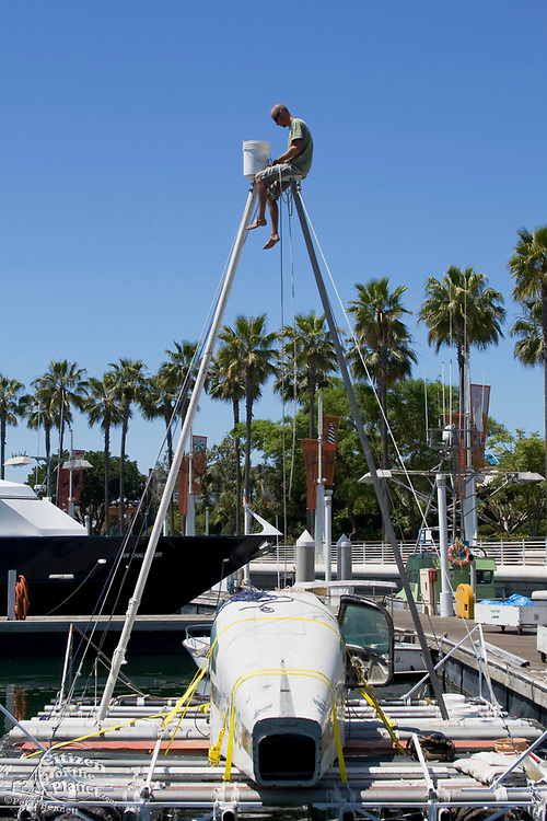 """Joel Paschal rigs the halyard in preparation for the maiden voyage of the """"Junk"""" raft, out of Long Beach Harbor. 5/18/08.  in June of 2008, the raft named """"Junk""""  will sail 2,100 miles from Los Angeles to Hawaii to bring attention to the plastic marine debris (nicknamed the plastic soup) accumulating in the North Pacific Gyre. Designed by Dr. Marcus Eriksen and Joel Paschal, the raft is constructed from 20,000 plastic bottles, an airplane fuselage, discarded fishing nets, a solar generator, and a bicycle generator. California, USA"""