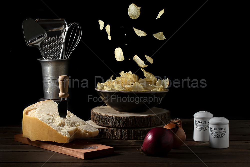 Potato chips falling in a bowl on a table with parmesan cheese onions salt and pepper