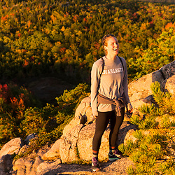 """A young woman enjoys the view from the trail on """"The Beehive"""" in fall in Maine's Acadia National Park."""