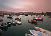 Saint Ives Harbour in Cornwall on the South West Coast of England on a misty foggy evening with the boats gently moving in calm water wtih the Village in the background