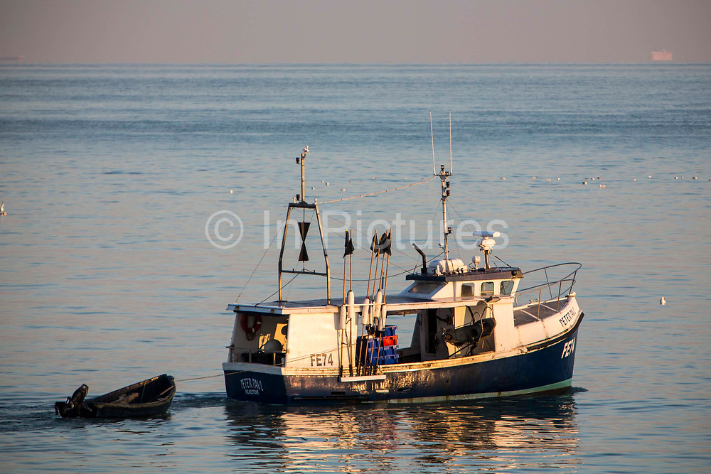 A British fishing boat arriving back into Folkestone Harbour at sunset after laying pots for crab and lobsters in the English Channel.