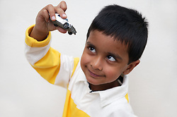 Young boy playing with a car,