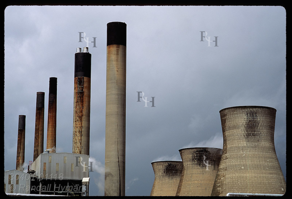 Cooling towers and row of smokestacks loom against stormy sky at industrial complex; Grangemouth. Scotland