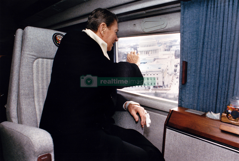 """Former United States President Ronald Reagan waves from Nighthawk 1 as he takes one last aerial tour of Washington, DC before heading home to California on Inauguration Day, January 20, 1989. The helicopter flew from the grounds of the US Capitol to Andrews Air Force Base. In the background is the US Capitol. A Marine helicopter which has the sitting President aboard uses the call sign """"Marine One."""" In this case, since Mr. Reagan was no longer the sitting President the helicopter was known by the call sign """"Nighthawk 1"""" for the Marine Helicopter Squadron One (HMX-1), nicknamed the """"Nighthawks."""" Photo by Pete Souza / White House via CNP /ABACAPRESS.COM"""