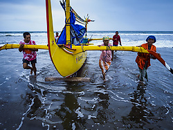 July 29, 2017 - Airkuning, Bali, Indonesia - Villagers land an outrigger fishing canoe in Kuning, a Muslim fishing village on the southwest corner of Bali. Villagers said their regular catch of fish has been diminishing for several years, and some mornings return without any fish. (Credit Image: © Jack Kurtz via ZUMA Wire)
