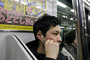 young adult person sitting in subway Tokyo Japan