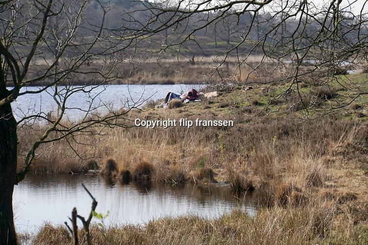 Nederland, Overasselt, 26-3-2020  In het natuurgebied de Hatertse Vennen bij Nijmegen wandelen mensen en laten hun hond uit. Door de opgelegde social distancing vanwege het coronavirus  houdt iedereen goed afstand van elkaar. Het is niet erg druk en dat gaat goed . Het gebied is enkele jaren geleden door staatsbosbeheer uitgedund om de grondwaterstand te verhogen en de vennen en hei nieuw leven in te blazen.Foto: Flip Franssen