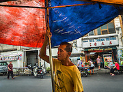 "15 NOVEMBER 2016 - GEORGE TOWN, PENANG, MALAYSIA: A street food vendor sets up his umbrella on Kimberly Street, one of George Town's better known ""food streets."" George Town is a UNESCO World Heritage city and wrestles with maintaining its traditional lifestyle and mass tourism.           PHOTO BY JACK KURTZ"