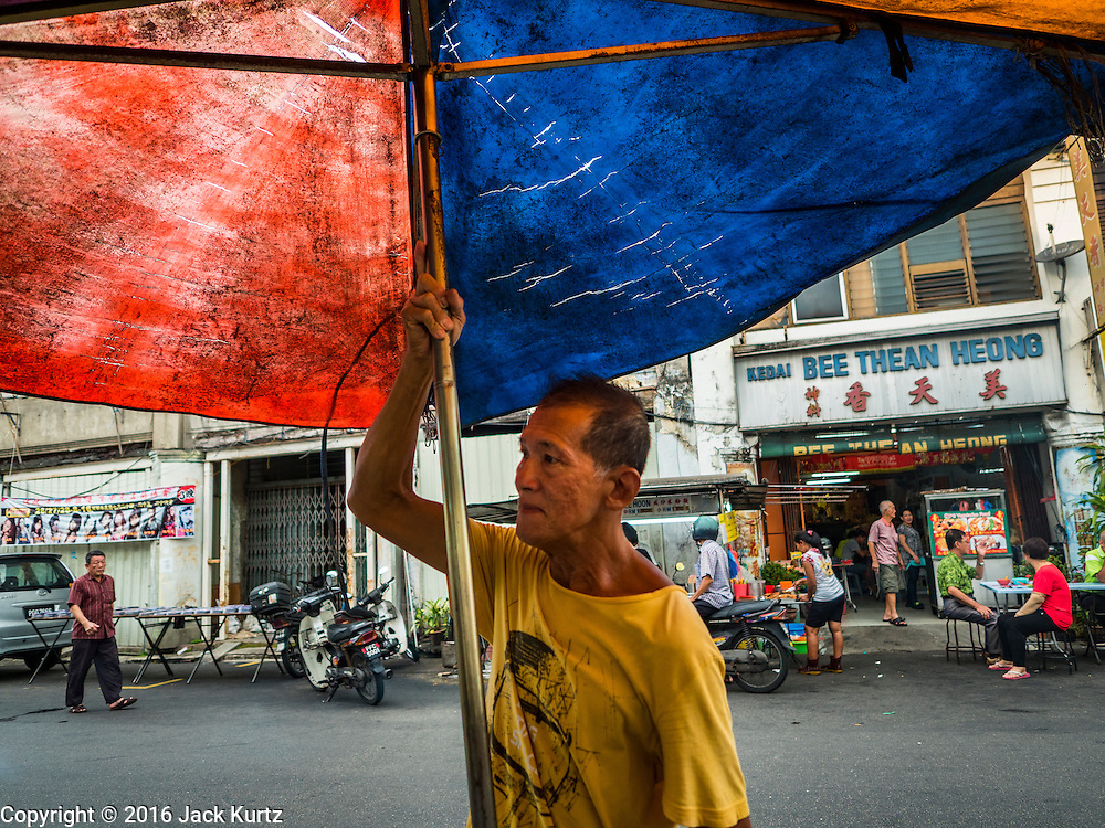 """15 NOVEMBER 2016 - GEORGE TOWN, PENANG, MALAYSIA: A street food vendor sets up his umbrella on Kimberly Street, one of George Town's better known """"food streets."""" George Town is a UNESCO World Heritage city and wrestles with maintaining its traditional lifestyle and mass tourism.           PHOTO BY JACK KURTZ"""
