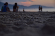 Before sunrise, early morning on a part of China beach in Danang. Only the sand is in focus and we can guess some people seated on the beach and walking.