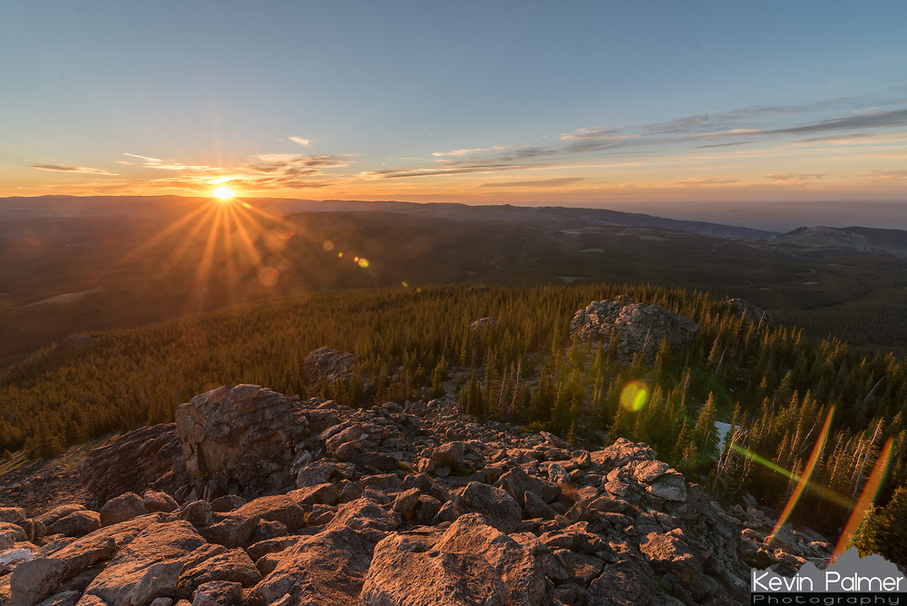 The setting sun casts a golden glow on the boulders beneath the summit of Black Mountain.