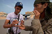 Mcc0030300 . Daily Telegraph..Young rebel volunteers light cigaretes after Rebel forces retook the  town of Binjawwad. .Gaddafi's forces have been on forced retreat since saturday night due to repeated attacks from NATO airstrikes and are now holding ground approximately.60 miles from Sirt ...Binjawwad 29 March 2011