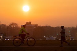 © Licensed to London News Pictures. 20/04/2021. London, UK. Members of the public exercise during sunrise on Blackheath Common in South East London. Temperatures are expected to rise with highs of 16 degrees forecasted for parts of London and South East England today . Photo credit: George Cracknell Wright/LNP