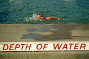 A male swimmer performs the Crawl across this scene of frewsh water bathing in the Serpentine Lake in London's Hyde Park. As the man twists his head to gulp in air, breathing a lungful of oxygen, he passes the lettering stencilled on the poolside warning of shallow water. This bathing area is where the normally busy Serpentine Swimming Club has the use of this Royal Lake known as Lansbury's Lido. It is now normally open only in the summer, but one traditional event occurs each year on New Year's Day, when the ice is broken and brave bathers dive into the cold waters of the lake. The Serpentine will be used for the swimming leg of the triathlon at the London 2012 Olympics. The pool was formed in 1730, its name from a snakelike, curve. Queen Caroline wife of George II ordered the damming of the River Westbourne and other natural ponds in Hyde Park.