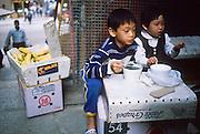 01 DECEMBER 1988   - HONG KONG: Children snack in an alley in Hong Kong.   PHOTO © JACK KURTZ  children  family  lifestyle  poverty