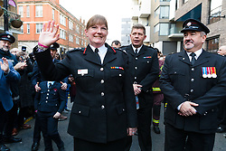 © Licensed to London News Pictures. 23/12/2019. London, UK. London Fire Commissioner (LFC), Dany Cotton waves as she is greeted by members and family of the Fire Brigade on her final day in office. Hundreds of firefighters lined Union Street in London today to provide a Guard of Honour on the final day in office for London Fire Commissioner, Danny Cotton. Photo credit: Vickie Flores/LNP