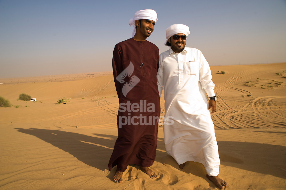 Two local men, in traditional dress, in the desert.