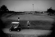 Men get out of a golf cart and walk up to a verdant putting green at a desert golf course on the edge of Las Vegas, Nevada, USA.