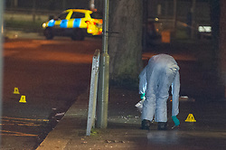 © Licensed to London News Pictures. 20/12/2019. London, UK. A forensic investigator gathers evidence on Courtland Avenue after reports of a fight, two males suffering stab wounds were later located a short distance away where one male died. Police were called to Courtland Avenue, NW7, at 20:11GMT following a report of a fight in progress. Officers attended however no trace of any victim or suspects was found. At 20.27GMT, police were called by the London Ambulance Service to Barnet Bypass, near Scratchwood Park, to reports of a man, in his 20s, with stab injuries. Officers attended. The man was treated at the scene by paramedics before being taken to hospital. After a search of a car found at the scene, a man, in his 30s, was found inside a vehicle with stab wounds. Despite the efforts of emergency services, he was declared dead a short time later.. Photo credit: Peter Manning/LNP