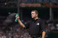 """Major League Baseball umpire Ron Kulpa sprays bug spray into the air during Game 2 of the 2007 ALDS at Jacobs Field in Cleveland. In what has become known at the """"Bug Game,"""" midges infested the infield during the game but seemed to bother the visiting Yankees more than Cleveland."""