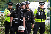 Thames Valley police officers and an enforcement agent monitor environmental activists from HS2 Rebellion on the other bank of the river Colne during a large policing operation to ensure the removal of an ancient alder tree as part of works for the HS2 high-speed rail link on 24th July 2020 in Denham, United Kingdom. Officers from the Metropolitan Police, Thames Valley Police, City of London Police and Hampshire Police were in attendance as well as enforcement agents from the National Eviction Team.