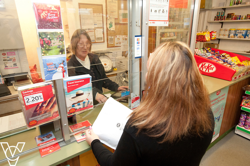 Pictured is postmaster Sarah Draisey serving customer Hannah Bee<br /> <br /> Shireoaks Post Office, Worksop.  Community Fund feature.<br /> <br /> Date: December 1, 2014