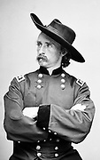 George Armstrong Custer (1839-1876) United States Army office and cavalry commander in American Civil War and Indian Wars. Defeated and killed at Battle of Little Bighorn in what iscalled Custer's Last Stand.  Photograph in uniform, seated.