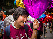 01 AUGUST 2013 - BANGKOK, THAILAND: A girl walks down a Bangkok street with a mylar balloon. This was in the neighborhood around Thammasat University, the second oldest university in Thailand, on the school's graduation day.    PHOTO BY JACK KURTZ