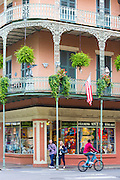 Tourists, typical architecture, wrought iron balcony and flag corner St Philip and Royal Street, French Quarter, New Orleans, USA