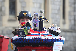 A warden looks at a knitted tapestry created by the Ickenham Postbox Toppers, in honour of the Duke of Edinburgh award, atop a post box in Windsor, Berkshire, following the death of the Duke of Edinburgh at the age of 99 on April 9. Picture date: Friday April 16, 2021.