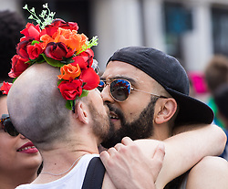 Portland Place, London, June 25th 2016. Thousands of LGBT people and their supporters gather for Pride in London, a colourful celebration of the hard-won rights of lesbian, gay, bisexual and transgender  people. PICTURED: Two men embrace  near Trafalgar Square.