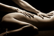 Hands of masseuse soothe the back of a woman