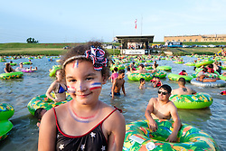 """Young girl with American flag face paint and swimsuit surrounded by people in floating tubes at the """"Rockin' the River"""" July 4th celebration on the Trinity Trails at the Panther Island Pavilion, Trinity River, Fort Worth, Texas, USA."""