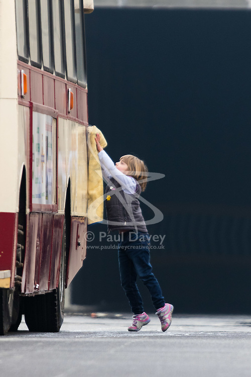 London, March 13th 2016. The annual St Patrick's Day Parade takes place in the Capital with various groups from the Irish community as well as contingents from other ethnicities taking part in a procession from Green Park to Trafalgar Square.  PICTURED: A child polishes a vintage bus prior to the procession. ©Paul Davey<br /> FOR LICENCING CONTACT: Paul Davey +44 (0) 7966 016 296 paul@pauldaveycreative.co.uk