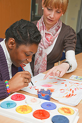 Black girl with Cerebral Palsy ( CP ) in painting class with care assistant at a resource for people with physical and sensory impairment.