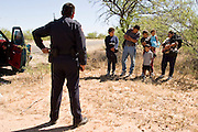05 MAY 2003 -- SELLS, AZ:  A Tohono O'Odham police officer talks to a family of undocumented immigrants from the Mexican state of Jalisco who he found hiding in the back of the passenger compartment of the pickup truck on the left. The driver of the truck was stopped by a Tohono OOdham tribal police officer for speeding on AZ 86 east of Sells, AZ, the capital of Tohono OOdham Indian Reservation, May 5, 2003. The Tohono OOdham reservation covers a vast expanse of Southern Arizona and has a 70 mile border with Mexico. In recent years the reservation has been flooded with undocumented immigrants who pass through the reservation on their way north to Phoenix, AZ, and other cities in the US. About 1,500 undocumented immigrants, most from Mexico, cross the reservation, which has more land than the state of Delaware,  every day. According to the tribal government, the tribal police department spends about 60 percent of its resources dealing with crime created by the undocumented immigrants. Many times tribal police officers have to wait hours for the US Border Patrol to respond to calls to pick up undocumented immigrants. This family was released by the tribal police two hours after the Border Patrol was notified that the police had the family. The Border Patrol didn?t respond the tribal police call.  PHOTO BY JACK KURTZ