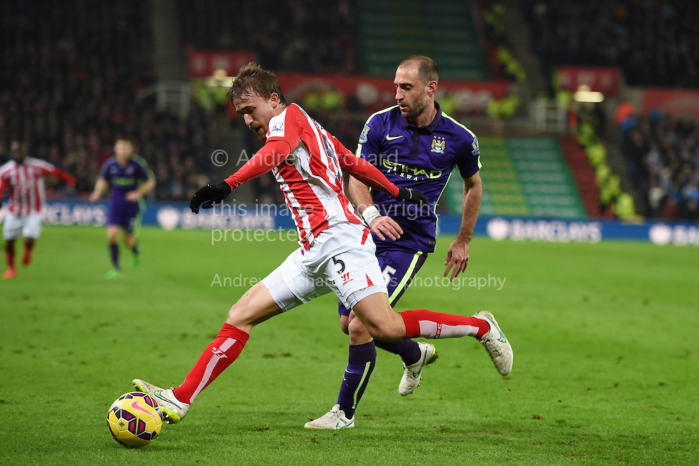 Marc Muniesa of Stoke city clears from Pablo Zabaleta of Man city. Barclays Premier League match, Stoke city v Manchester city at the Britannia Stadium in Stoke on Trent , Staffs on Wed 11th Feb 2015.<br /> pic by Andrew Orchard, Andrew Orchard sports photography.