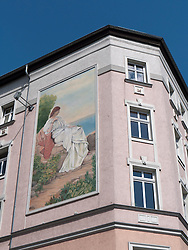 Large painting on facade of old apartment building in Berlin Germany